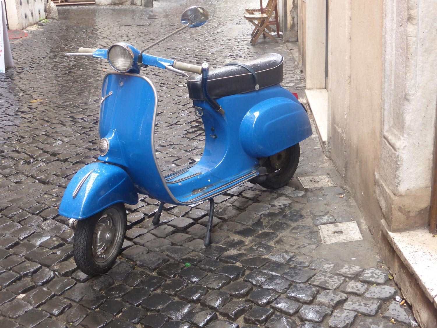 Blue Vespa in the cobblestone streets of Rome